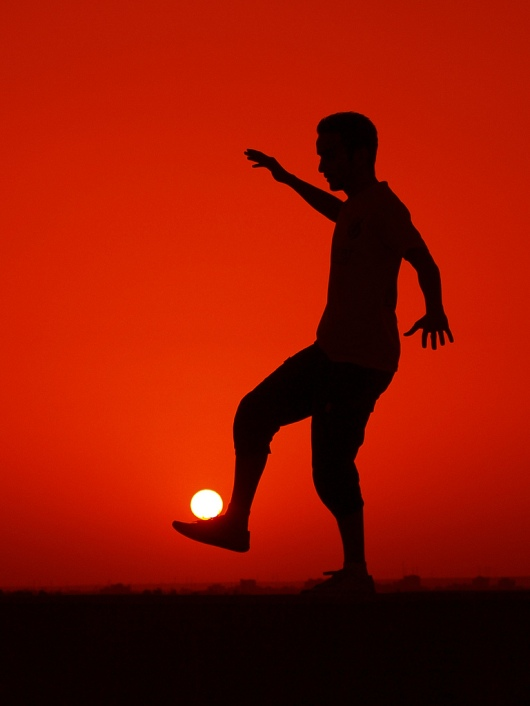 soccer player balances the sun